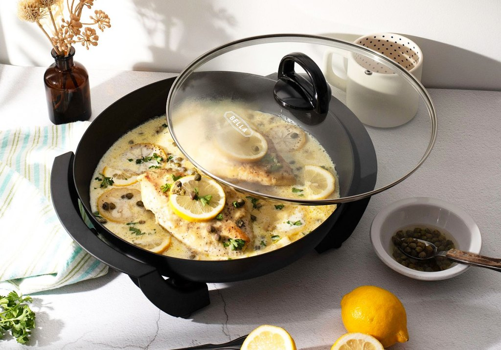 black round electric skillet on counter with lemon chicken dish cooking inside with a glass cooking lid
