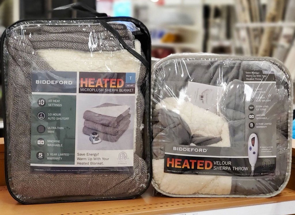 two heated sherpa blankets on wood shelf at store