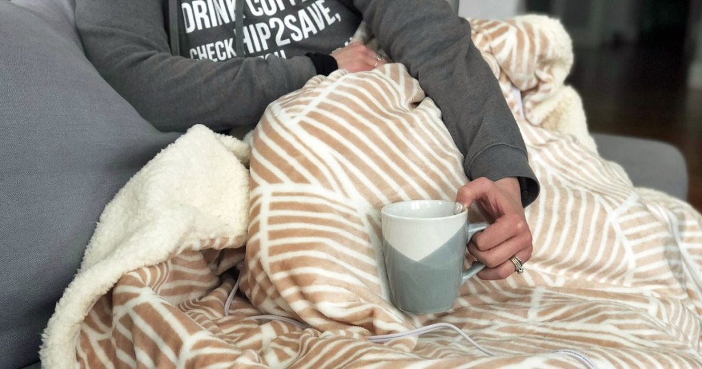 woman in grey sweatshirt under an electric blanket holding a coffee mug