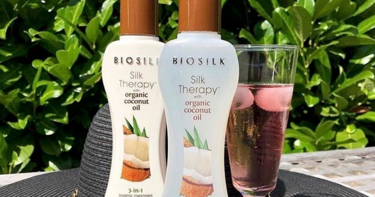 BioSilk Silk Therapy bottles on table with glass of wine next to them