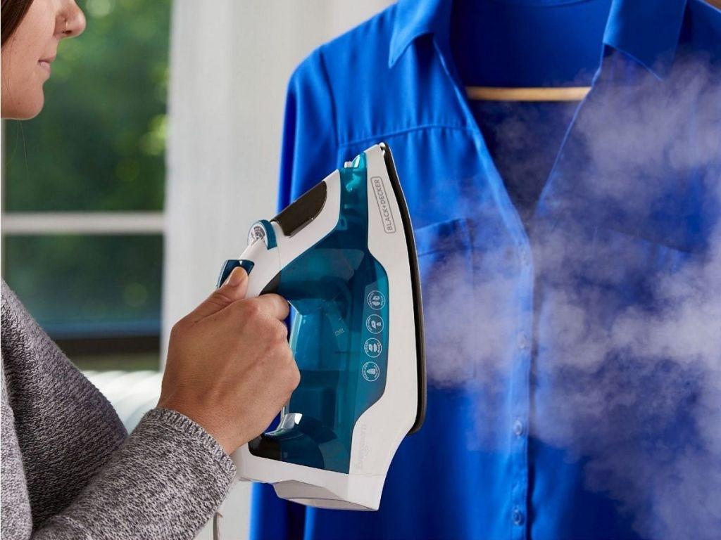 Woman using Black & Decker Steam Iron to steam shirt hanging on hanger