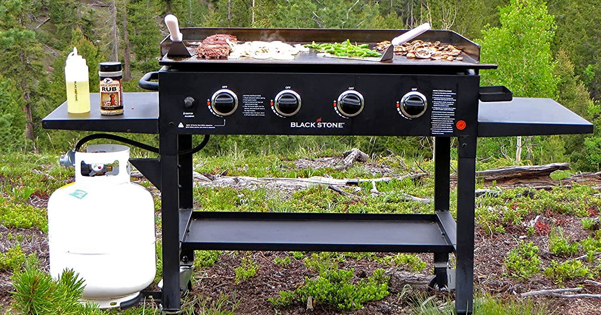 black blackstone griddle with food on the griddle and accessories on side shelf and white propane tank hooked up to it