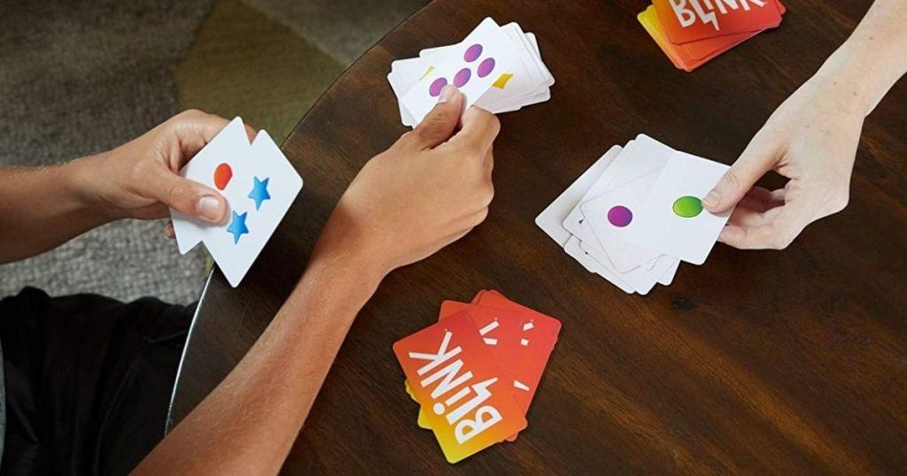 hands holding cards for Blink game