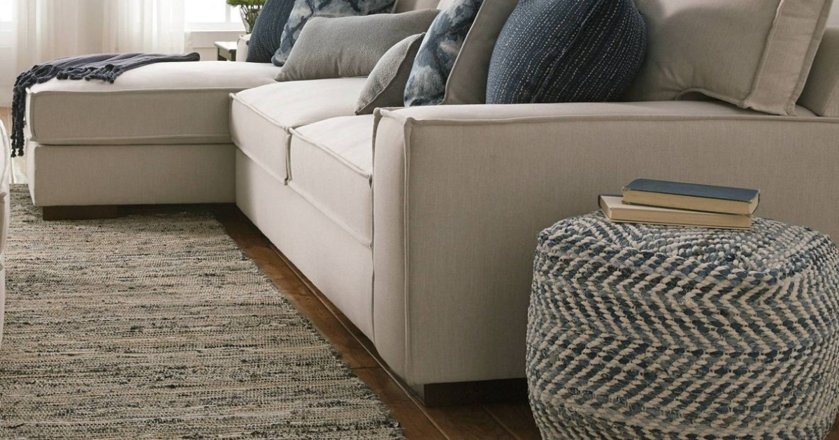 blue pouf next to a cream colored couch