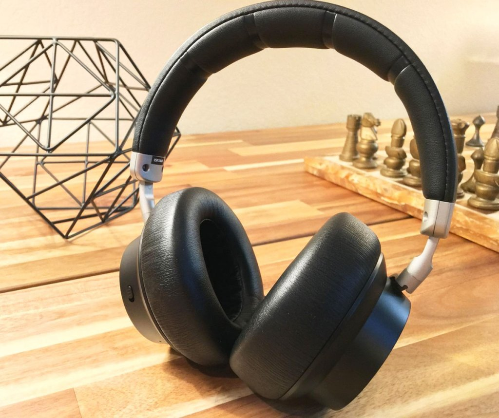 pair of black over the ear headphones on a wood table