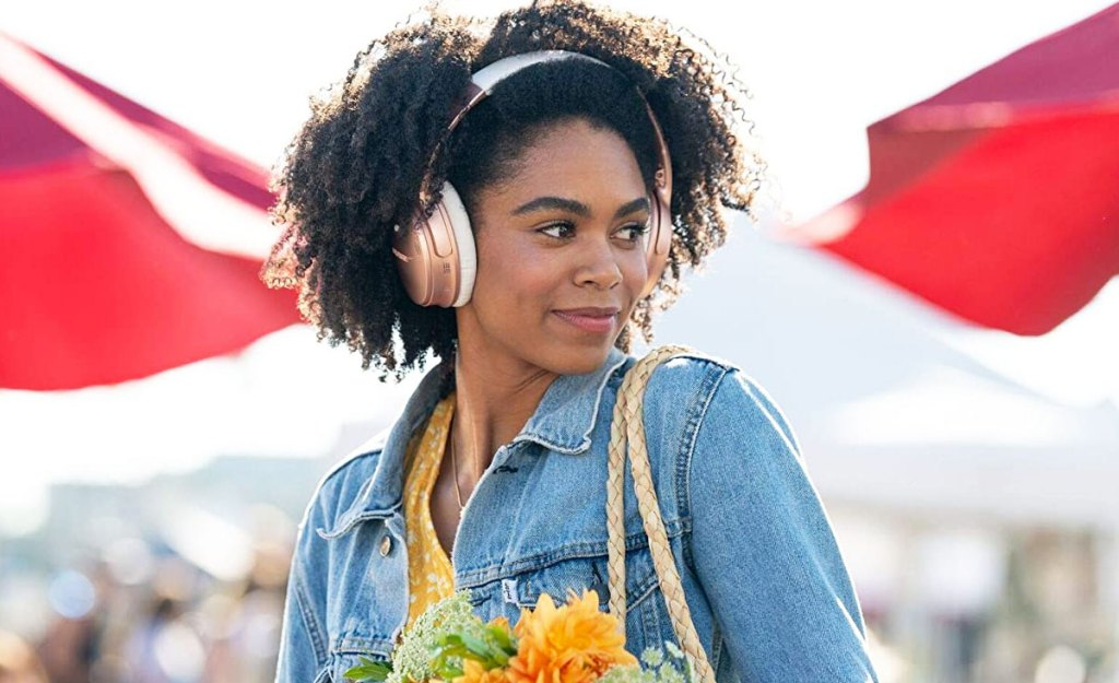 woman shopping at outdoor market wearing pair of pink bose headphones