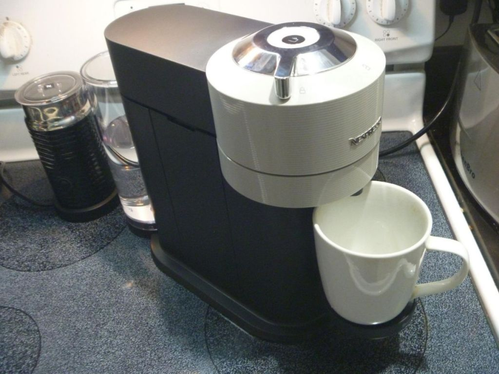 black and gray Nespresso machine with coffee cup