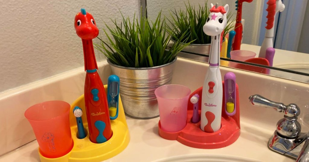 red dinosaur and white and pink unicorn themed kids electric toothbrush sets on bathroom counter