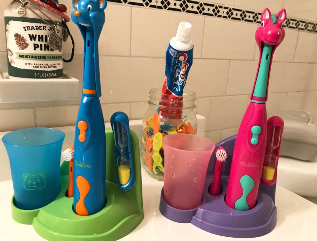 blue bear and pink horse themed kids electric toothbrush sets on bathroom counter
