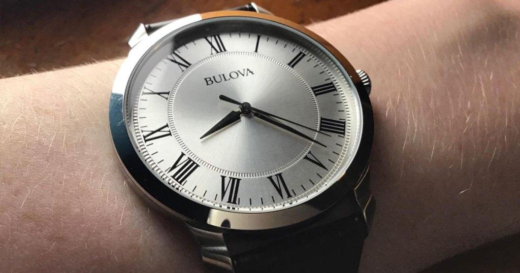 man's arm with a silver bulova watch on wrist