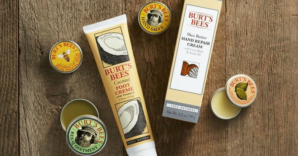 four tins and two tubes of burt's bees products laying on a wood table