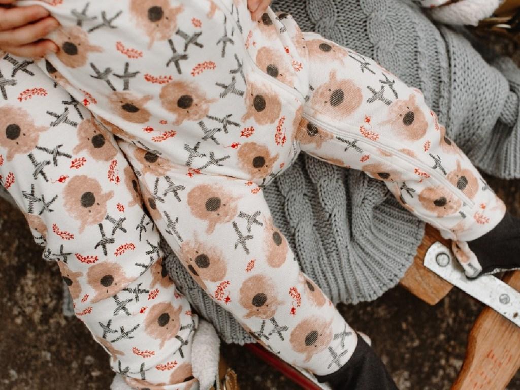 toddler sitting on a adult's lap wearing burts bees reindeer pajamas