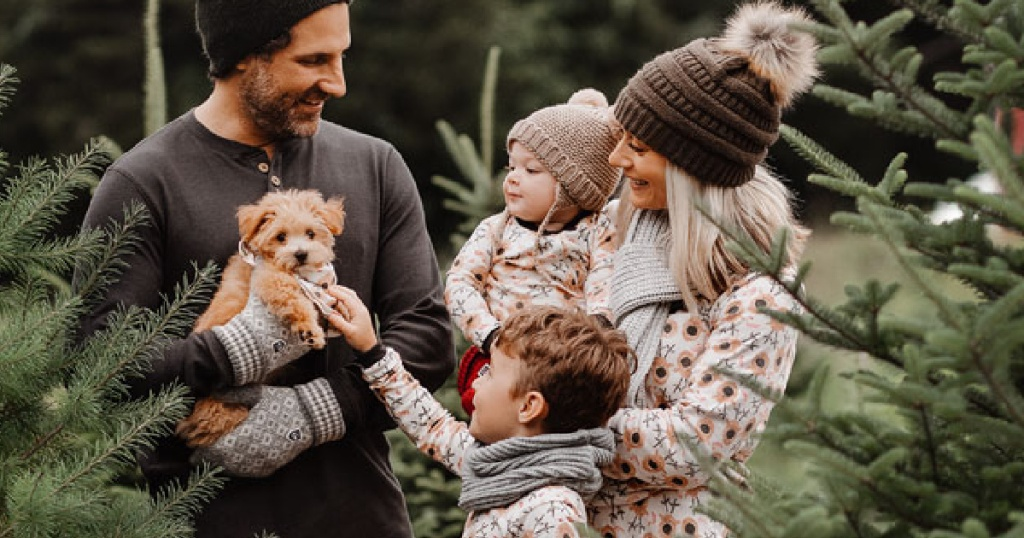Family standing outside wearing burt's bee reindeer pajamas