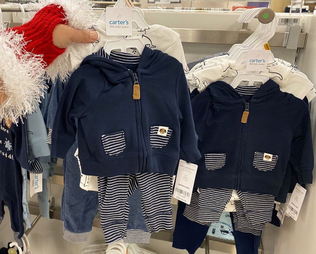 woman in santa glove holding up a blue carter's baby boy set