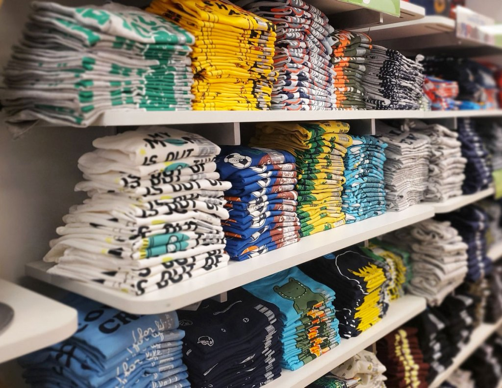 display of boys graphic shirts folded on white shelves