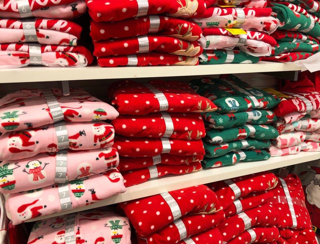 pairs of carter's christmas pajamas on white shelves