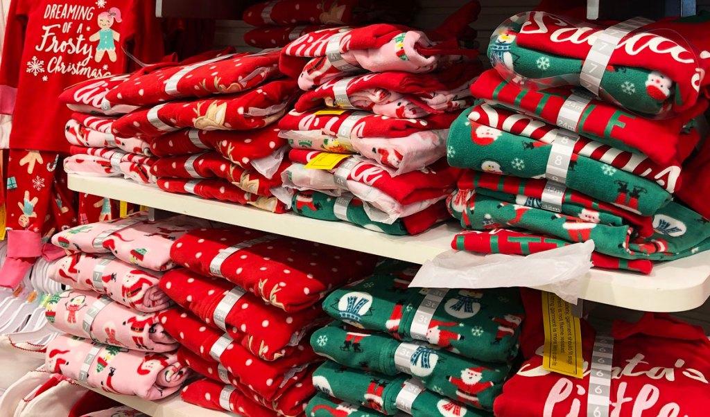 stacks of carter's christmas pajama sets on white shelves