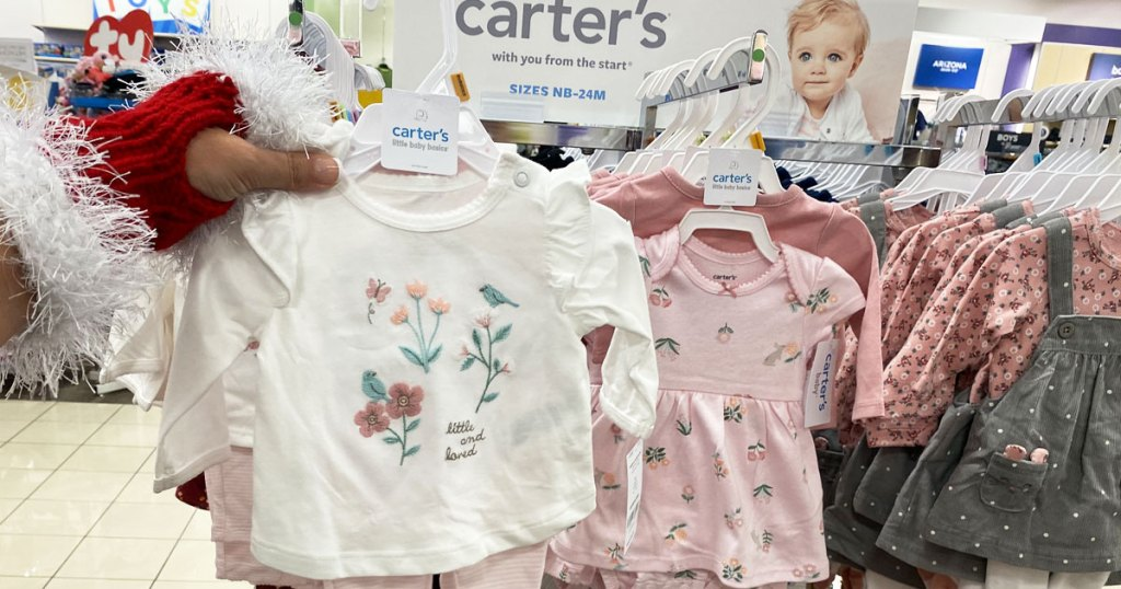 woman in santa glove holding up a white carters baby clothing set in front of carters display