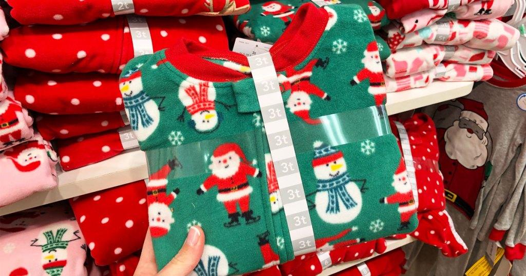 woman holding up green fleece pair of baby christmas pajamas
