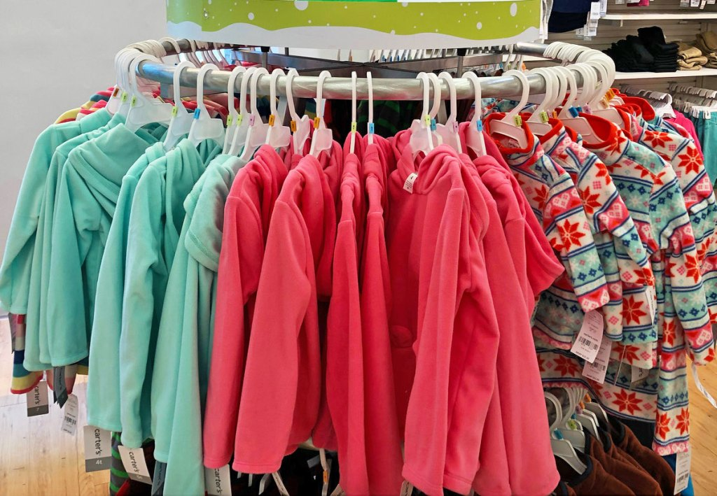 girls fleece jackets in various colors hanging on a round store display