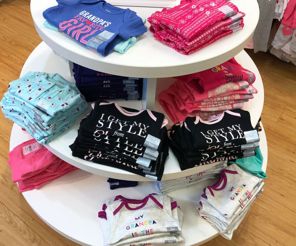 round store display with folded girls graphic tees