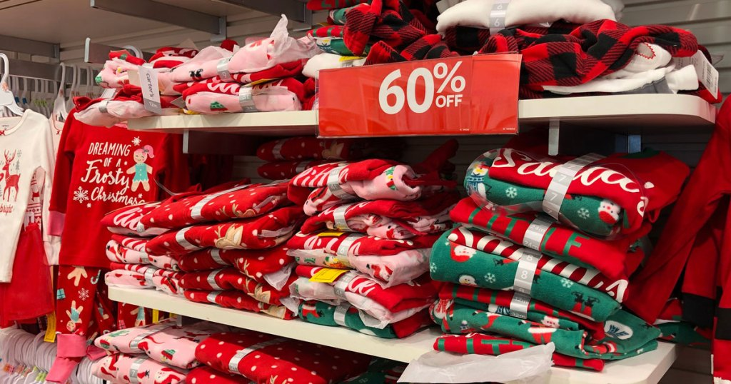 kids christmas pajama sets on white shelves with red 60% off sale sign