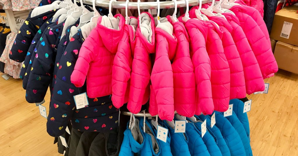 navy blue with hearts and plain pink and blue colored kids puffer jackets hanging on round display at carter's