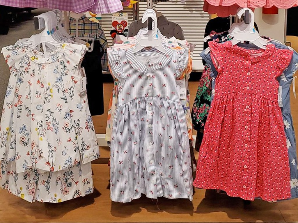 toddler girls dresses with flutter sleeves on hangers on a store display