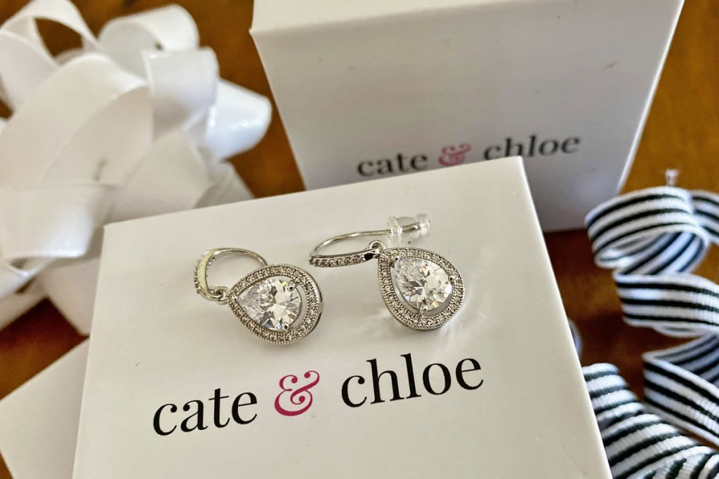 pair of white gold drop earrings on a white cate & chloe gift box with christmas ribbon and bow in background