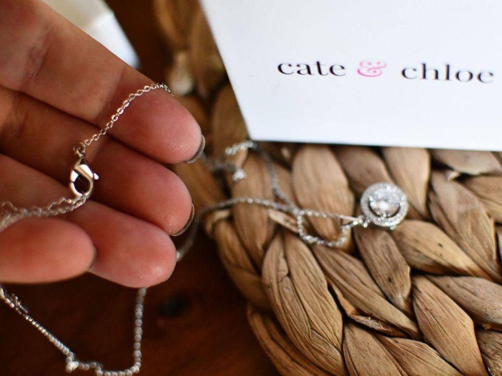 Tangan memegang kalung emas putih dengan jepitan di bagian depan dan kotak cate & chloe di latar belakang