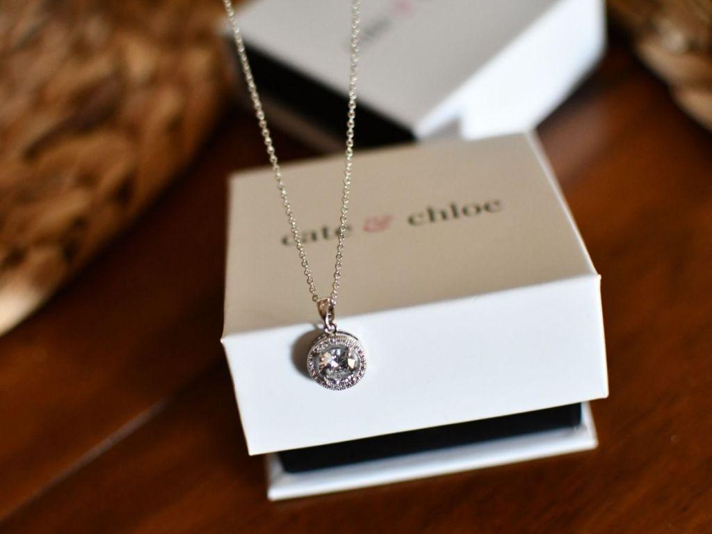 Kalung liontin lingkaran emas putih menjuntai di depan kotak perhiasan cate & cholie
