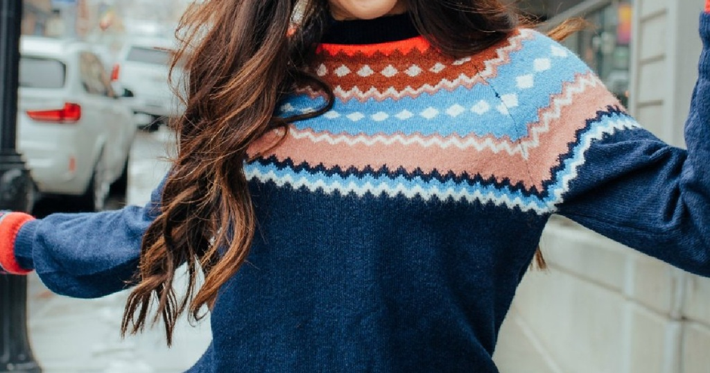 woman outside in blue, orange, red, and white patterned sweater
