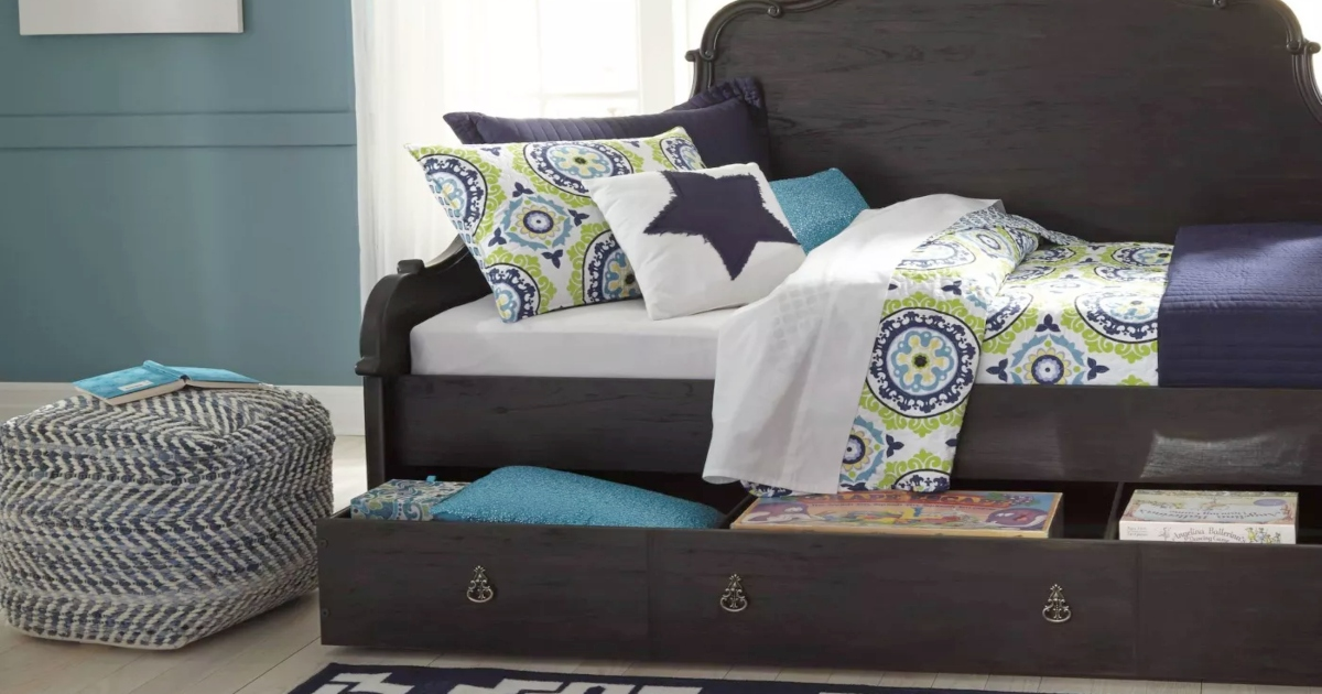 blue pouf next to a bed will pulled out drawer