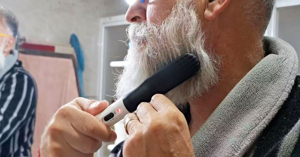 man standing looking in bathroom mirror using a heated comb on his beard