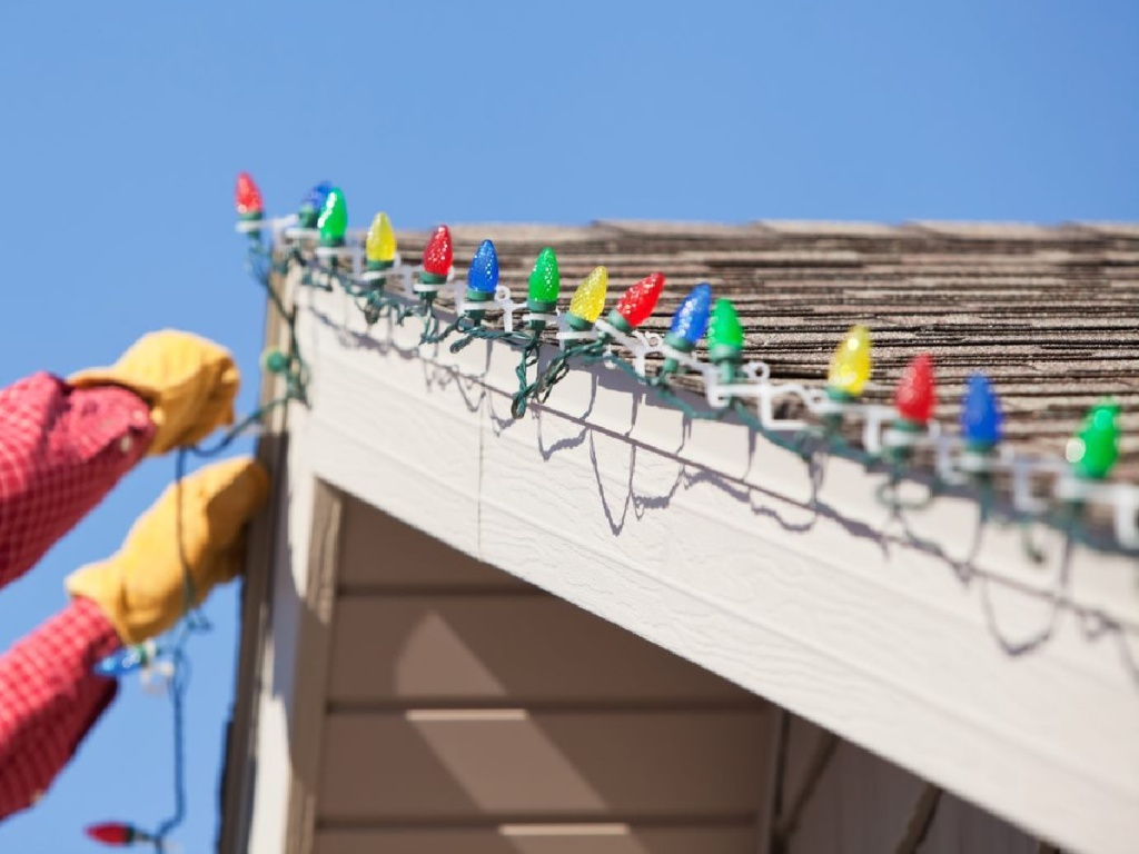 handyman hanging Christmas lights on home