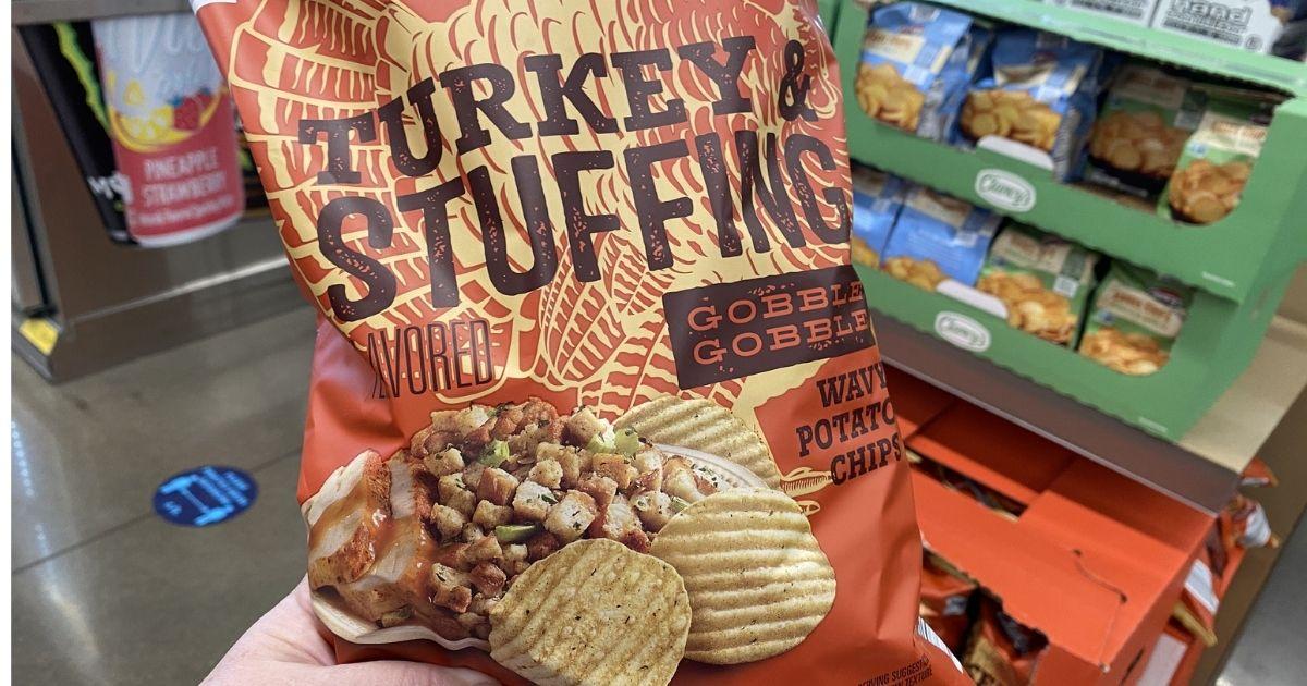 tangan memegang kalkun dan isian keripik kentang di toko