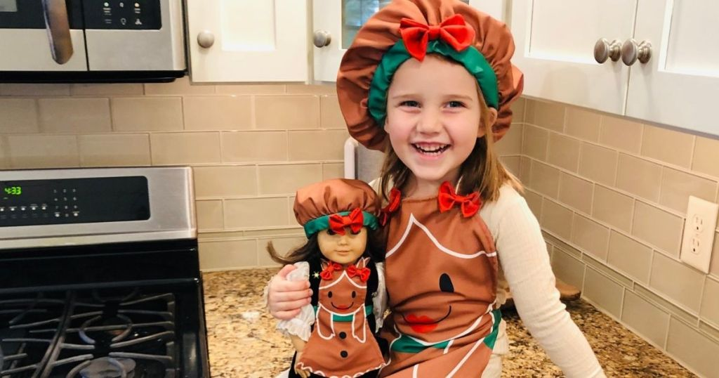 girl holding a doll in a matching outfit