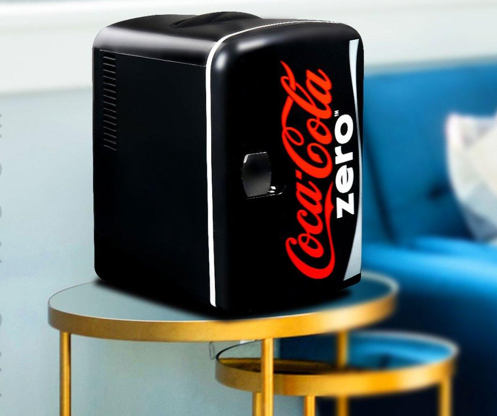 black coke zero themed mini fridge on an accent table near couch