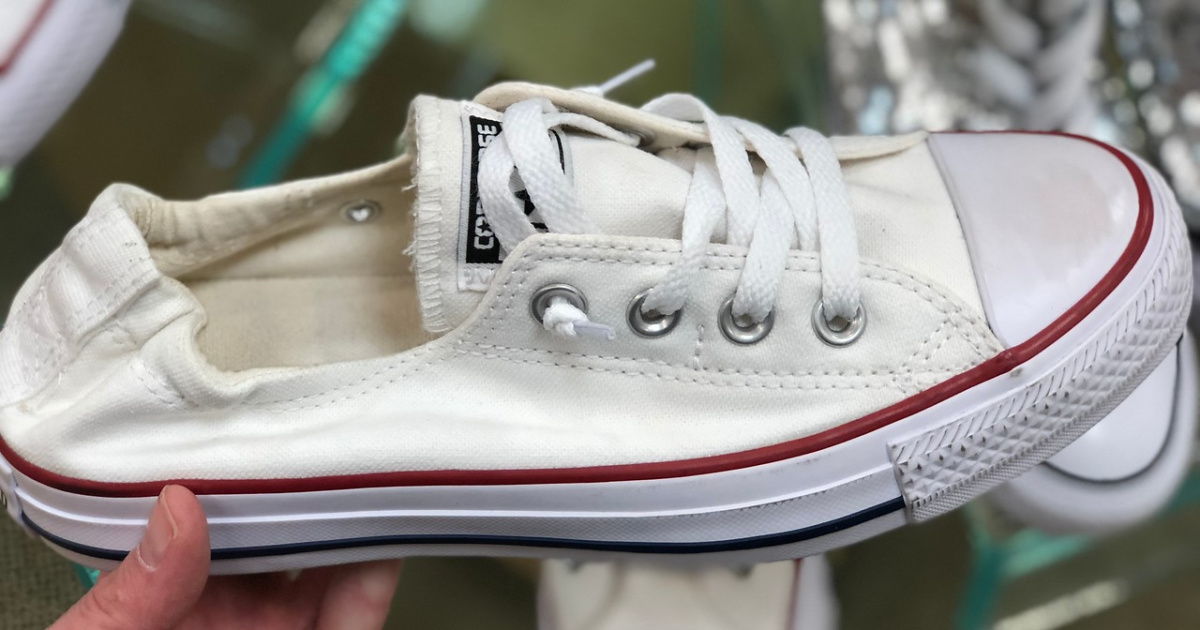 hand holding woman's white sneaker