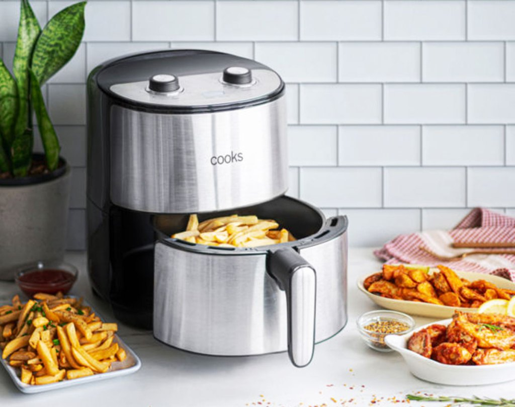 round stainless steel air fryer on kitchne counter with fries in basket and plates of fried foods around it