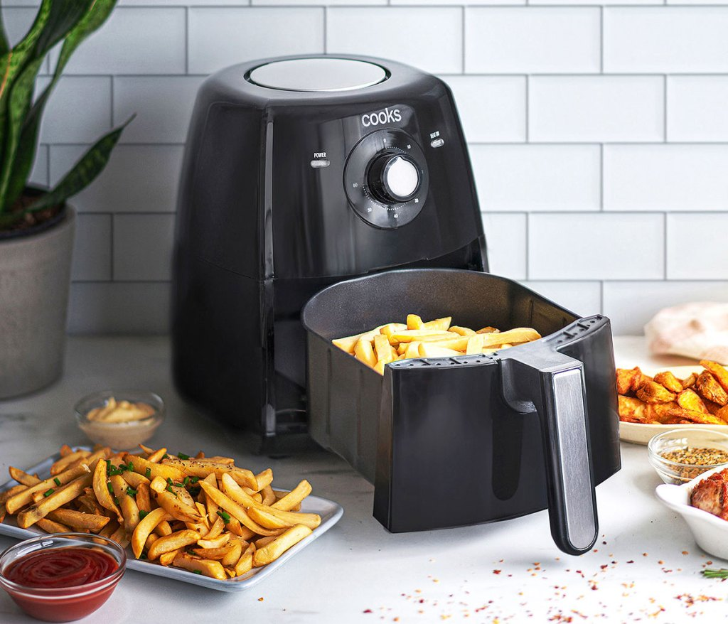 black air fryer on kitchne counter with fries in basket and fried food on plates around it