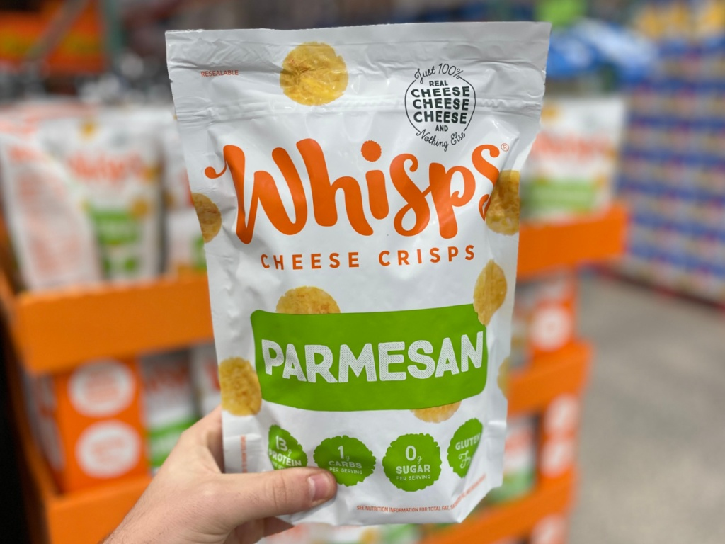 hand holding a large bag of parmesan whisp crackers at costco