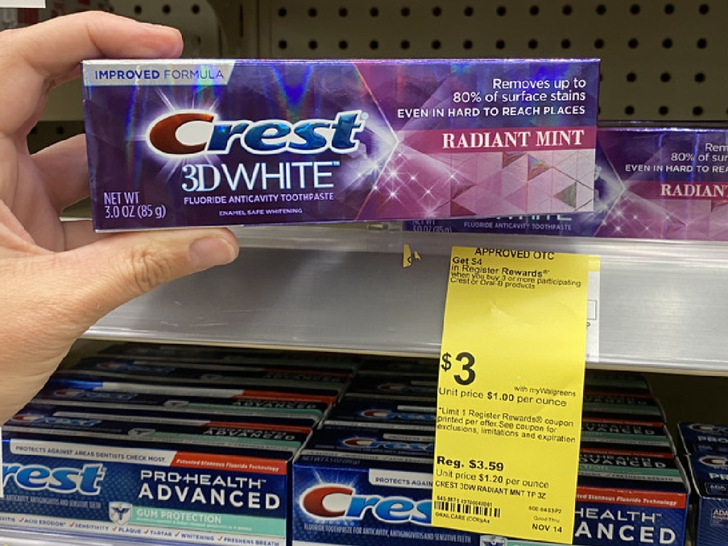 hand holding toothpaste in front of store shelf with sale sign