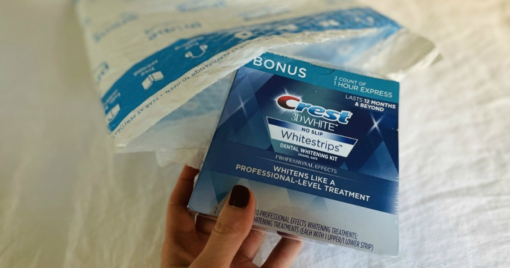 Woman taking box of Crest Whitestrips out of Amazon package