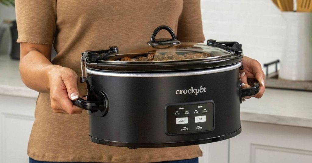 womans hands carrying black Crock Pot