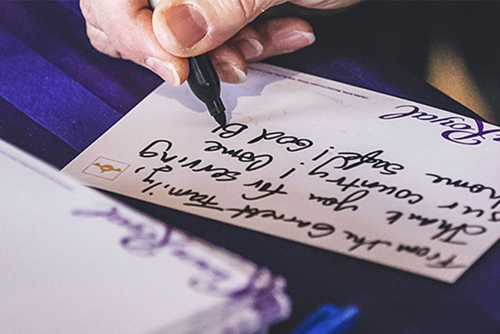 person using a black sharpie marker to write a note to include in a crown royal care package