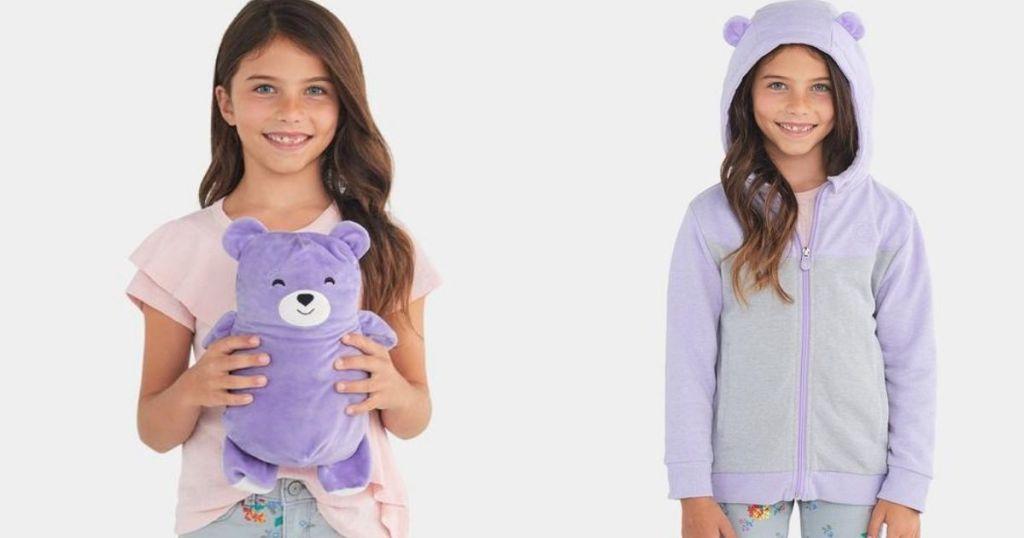 girl holding a plush bear next to girl in a sweatshirt