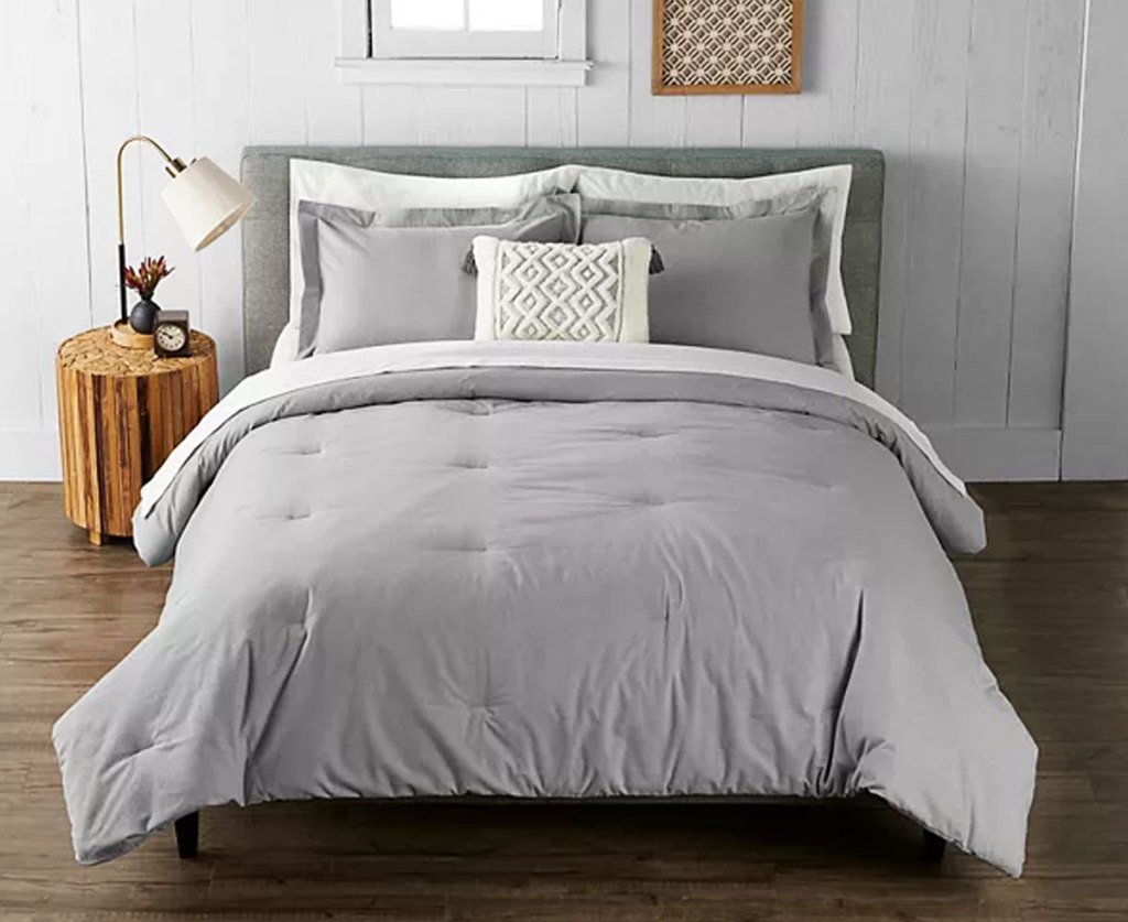 grey comforter set on a bed with matching pillow shams and coordinating throw pillow