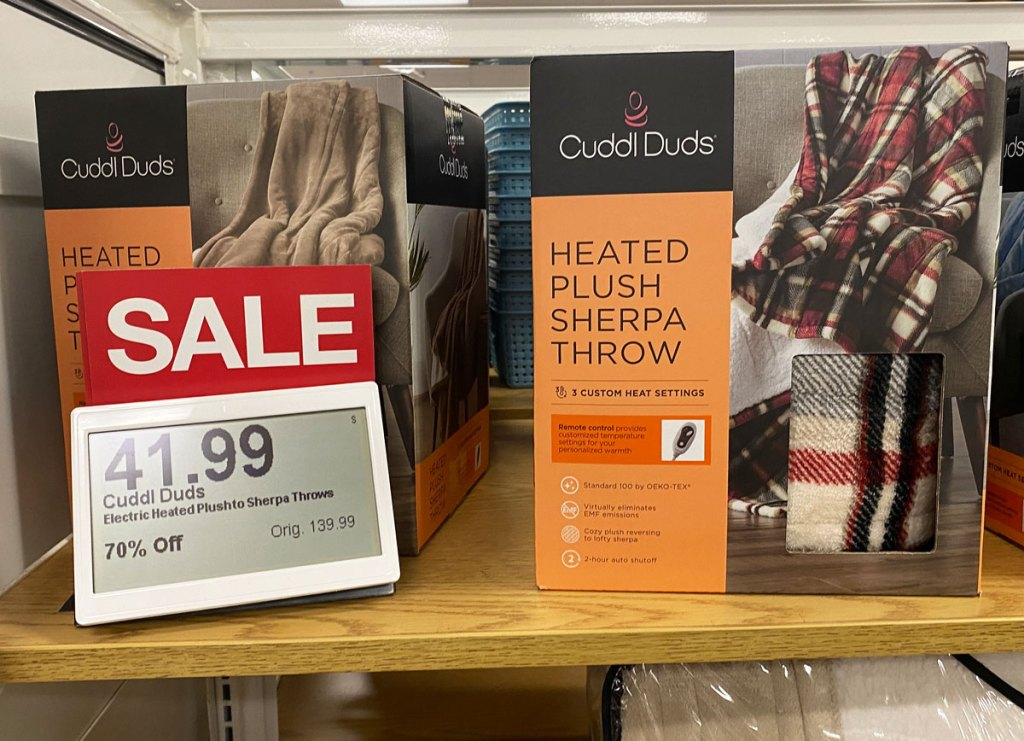 cuddl duds heated blanket on a wood shelf with $41.99 sale sign next to it