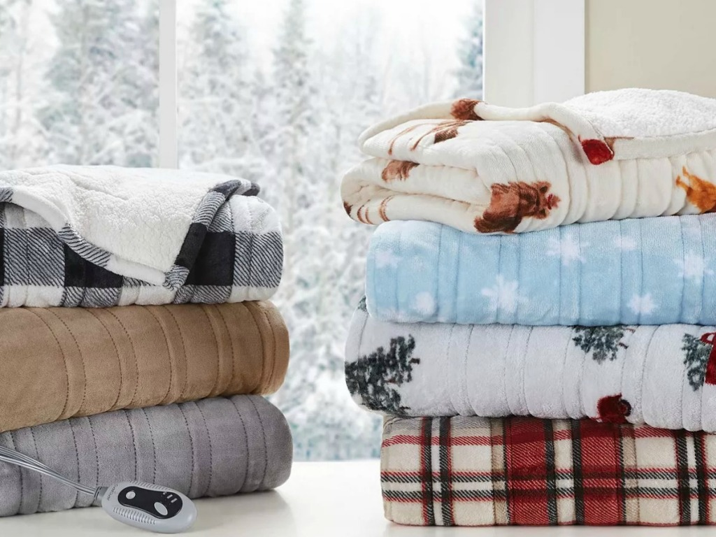 Cuddl Duds brand heated blankets in a variety of prints, folded and stacked